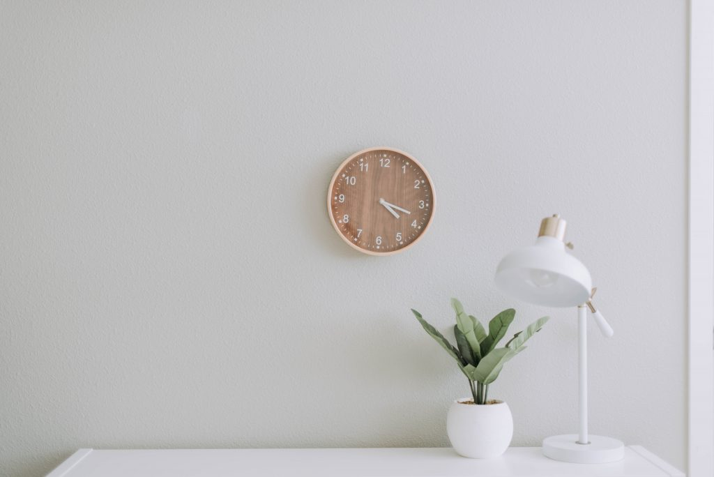 Minimalist white desk with lamp, plant and wall clock
